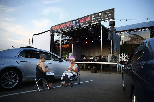 A couple of women enjoy their dinner outside of their vehicle before the concert begins. - CP PHOTO: JARED WICKERHAM