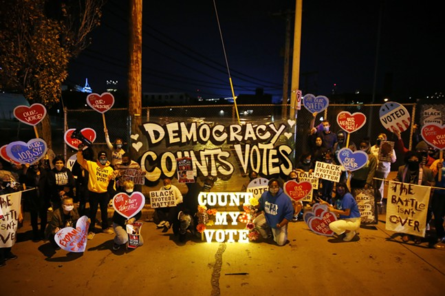 Organizers pose for a photo in front of one of many signs that lead the way to the Allegheny Elections warehouse in the North Side. - CP PHOTO: JARED WICKERHAM