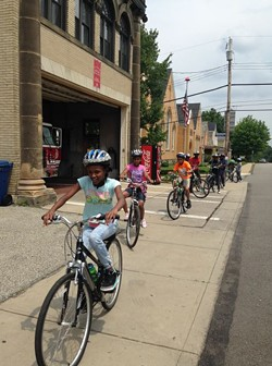 Middle school students ride bikes along Chartiers Avenue in Sheraden. - PHOTO BY RYAN DETO