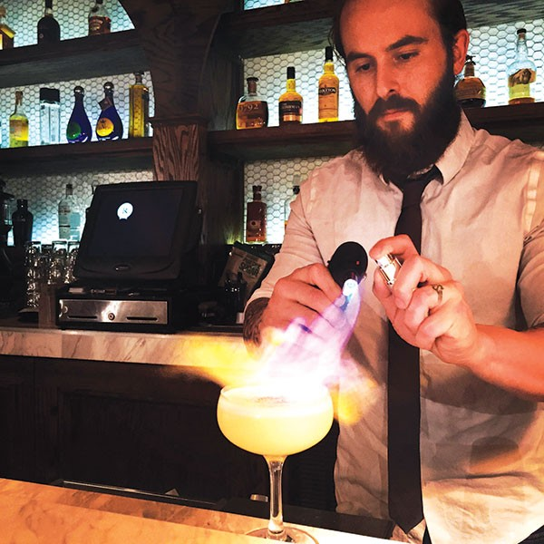 Corey Bardell flames his Mexican War Street cocktail. - PHOTO COURTESY OF ADAM DESIMONE
