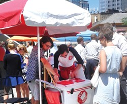 Todd Saulle, owner of The Pop Stop, and his employee, Mike Sestric, serve customers at the busy Farmers' Market in Market Square