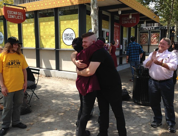 Conflict Kitchen worker Quinton Steele embraces a technical worker from Allegheny General Hospital, who was there in support of the restaurant's new union. - PHOTO BY RYAN DETO