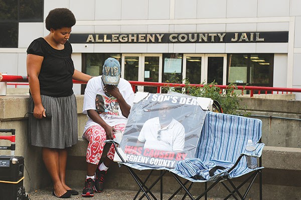 At a recent vigil, Julia Johnson consoles Tomi Lynn Harris, whose son died at the Allegheny County Jail in January. - PHOTO BY THEO SCHWARZ