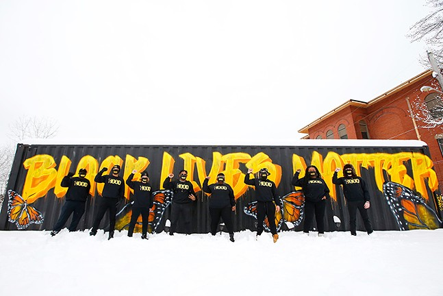 "Members of 1Hood pose in front of a Black Lives Matter mural painted by Pittsburgh artist Camerin ""Camo"" Nesbit - CP PHOTO: JARED WICKERHAM"