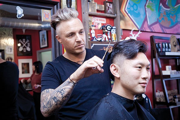 Co-ownerMichael Shurina (left) styles a customer - PHOTO BY HEATHER MULL