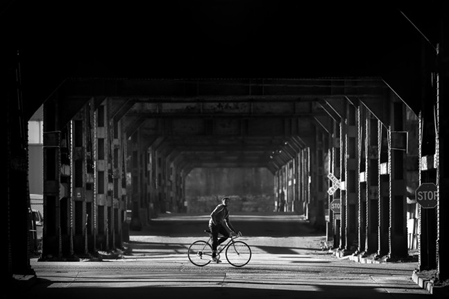 A man rides a bike down Smallman Street past an empty 33rd Street on the edge of the Strip District on Thu., April 2, 2020. - CP PHOTO: JARED WICKERHAM