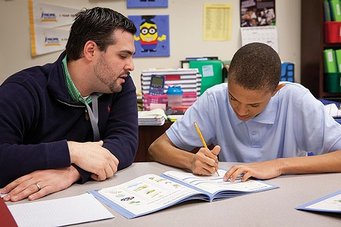 Esteban Sagastume helps a student with math at Propel East. - PHOTO BY HEATHER MULL