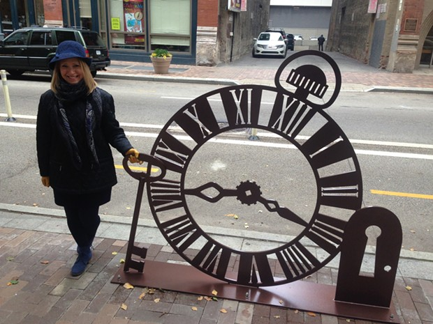 "Myra Falisz posing with her public-art bike rack, ""Time-traveling Mike."" - PHOTO BY RYAN DETO"