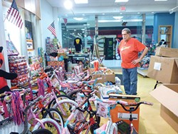 Jimmy Cvetic looks at the piles of donated toys in the Global Glorious Productions Monroeville Mall Office. - PHOTO BY ASHLEY MURRAY