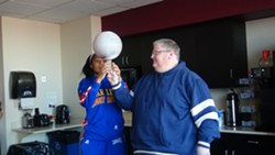 Harlem Globetrotter Sweet J teaches City Paper editor Charlie Deitch how to spin the basketball on his finger. - PHOTO BY ASHLEY MURRAY
