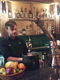 Zachary Maddox pours from the life-sized silver arm on Morcilla's bar top. - PHOTO BY CELINE ROBERTS