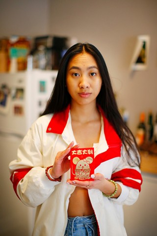 Michelle Truong poses with a red envelope (lì xì) she plans to give her friends for Lunar New Year, inside her East Liberty home on Fri., Feb. 5. - CP PHOTO: JARED WICKERHAM