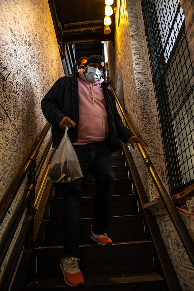 A shopper makes his way down the stairs of one of the Yinzers outlets in the Strip District. - CP PHOTO: KAYCEE ORWIG
