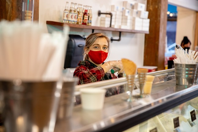 Jillian Kurta scoops ice cream for customers at Grandpa Joe's Candy Store. - CP PHOTO: KAYCEE ORWIG