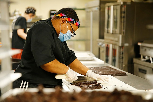 """Oliver Pinder, owner and chef at Wild Rise Bakery, prepares gluten-free brownies for Millie's Ice Cream, which will end up in their """"Blackout Brownie,"""" a collaboration with Pittsburgh artist Cue Perry. - CP PHOTO: JARED WICKERHAM"""