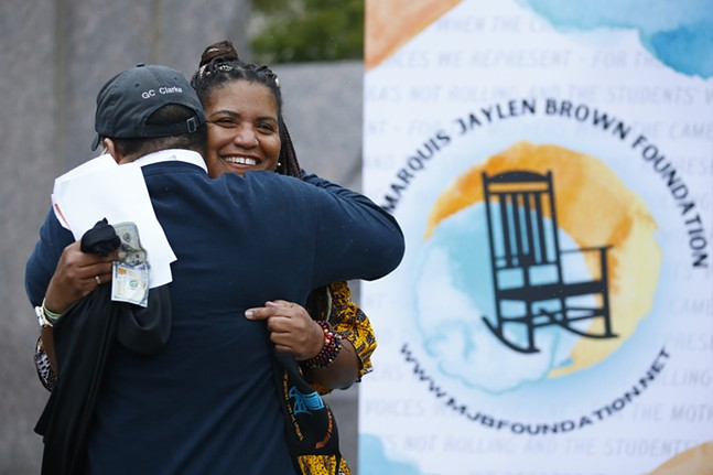 George Clarke, the father of Dannielle Brown, gets a hug after giving his daughter the first official donation to the Marquis Jaylen Brown Foundation. - CP PHOTO: JARED WICKERHAM