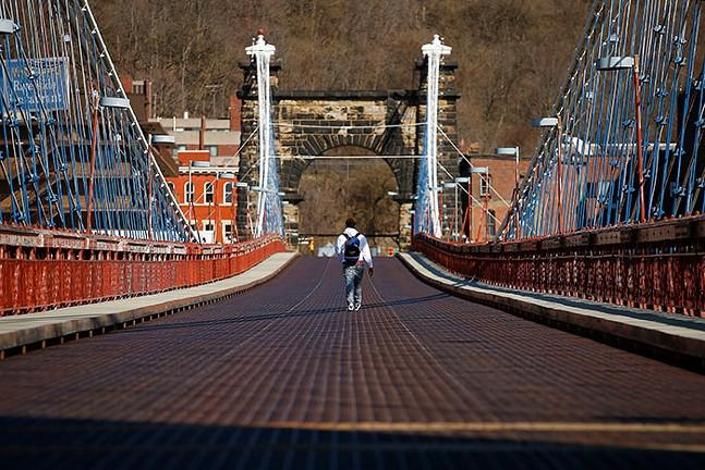 A man walks across the Wheeling Suspension Bridge in Wheeling, W. Va. - CP PHOTO: JARED WICKERHAM