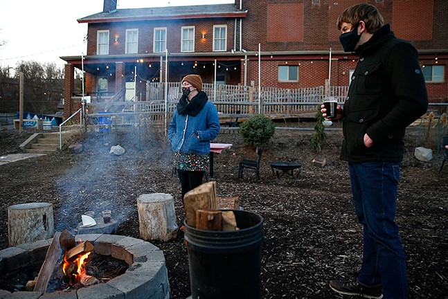 Carrie Wittig and Michael Cunningham enjoy beers in front of a fire pit at Spring Hill Brewing. - CP PHOTO: JARED WICKERHAM