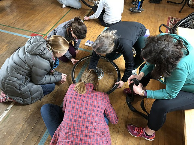 Attendees at a prior Bike PGH event demonstrate fixing a flat tire ahead of WMNBikePGH Workshop's Spring Tune Up. - PHOTO: EMILY KANE/BIKE PGH