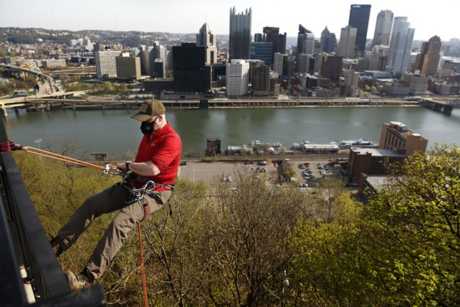 Matt Tolbert of the Explorers Club of Pittsburgh rappels down from the overlook as part of the Pittsburgh Parks Conservancy's 28th annual Emerald View Park cleanup event in Mount Washington on Sat., April 10. - CP PHOTO: JARED WICKERHAM