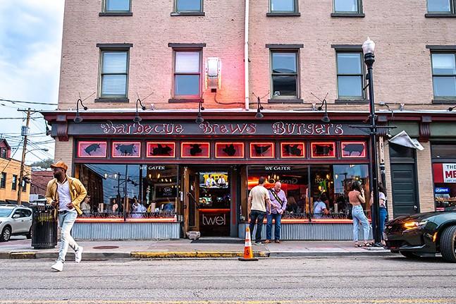 People lingering outside of Twelve Whiskey BBQ. - CP PHOTO: KAYCEE ORWIG