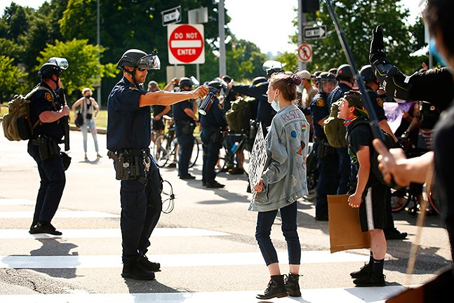 A Pittsburgh Police officer holds a  pepper spray canister up to a protester in Downtown Pittsburgh on July 4, 2020 - CP PHOTO: JARED WICKERHAM