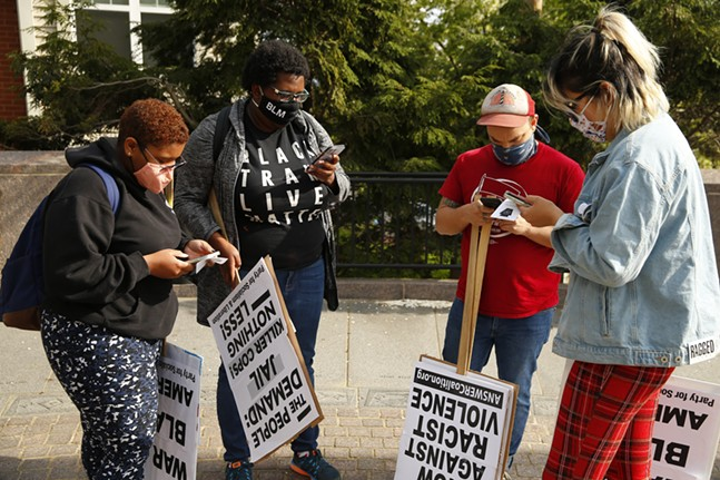 Protesters check their phones at Freedom Corner while the guilty verdict was announced against Derek Chauvin in the murder of George Floyd. - CP PHOTO: JARED WICKERHAM