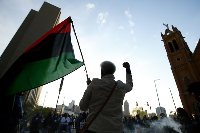 Frankie Harris of the Ujamaa Collective raises a fist and holds up a flag in front of the crowd gathered at Freedom Corner. - CP PHOTO: JARED WICKERHAM