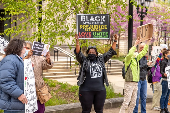 Nicol Porter, Minister of Music at Eastminster Presbyterian Church, cheers at honking cars during a Racial Justice Vigil outside of East Liberty Presbyterian Church. - CP PHOTO: KAYCEE ORWIG