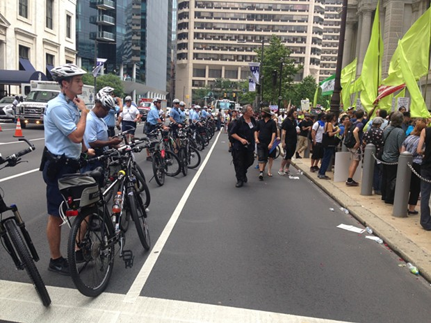 Police observing the lead up to a Green Party march, some officers are on their cell phones. - PHOTO BY RYAN DETO
