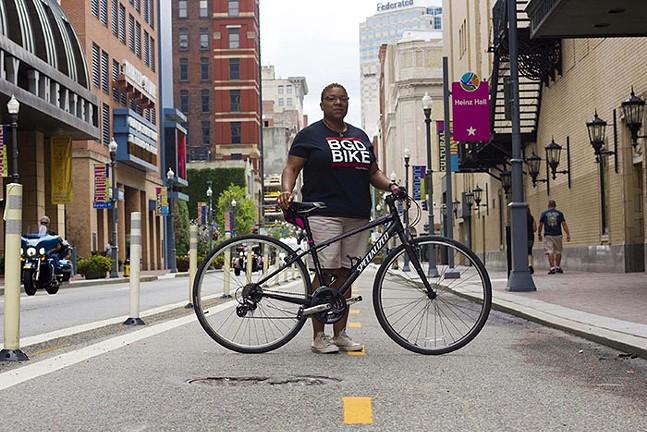 Black Girls Do Bike founder Monica Garrison on Penn Avenue bike lanes in the center of Pittsburgh's theater district. - PHOTO: CHANCELOR HUMPHREY