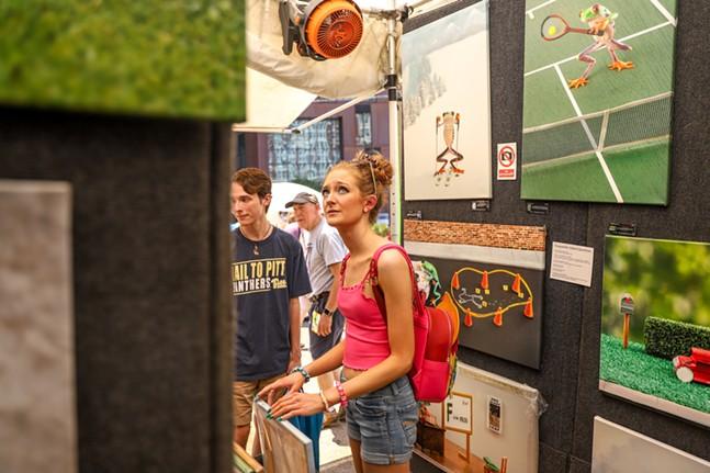 Festival goers admire frog photographs by Steven Daniel. - CP PHOTO: KAYCEE ORWIG