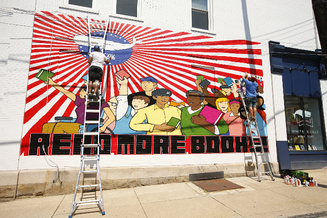 Brian Gonnella (right) and Jerome Charles work on alterations to White Whale Bookstore's mural on Fri., June 25, 2021. - CP PHOTO: JARED WICKERHAM