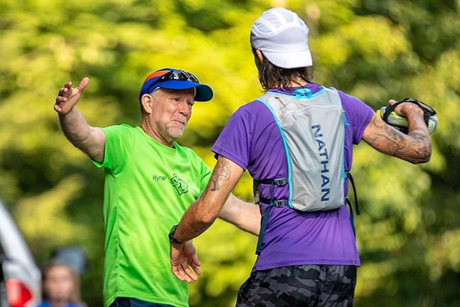 Greg Brunner embraces his dad at aid station number 3 during mile 16 of the Baker Trail Ultra Challenge. - CP PHOTO: KAYCEE ORWIG
