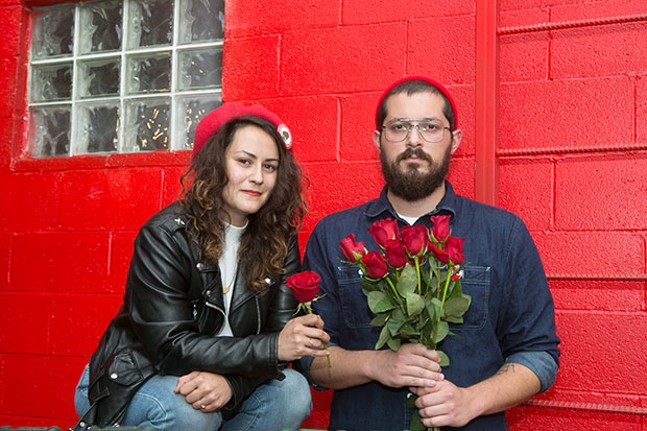 Pittsburgh Democratic Socialists of America co-chairs Arielle Cohen and Adam Shuck holding red roses, the symbols of democratic socialism - CP PHOTO BY JOHN COLOMBO