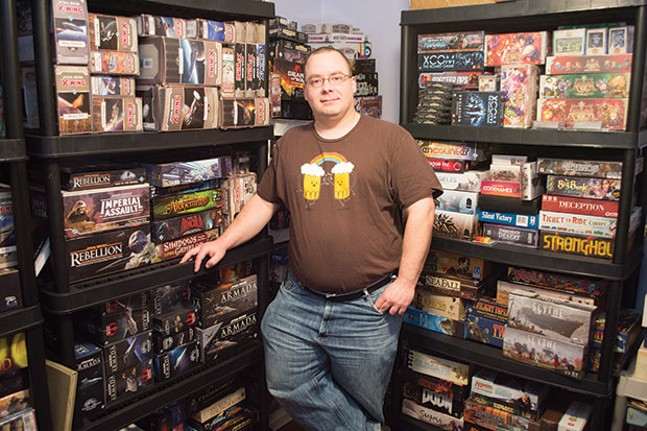 Dustin Felix at home, with part of his board-game collection - CP PHOTO BY JAKE MYSLIWCZYK