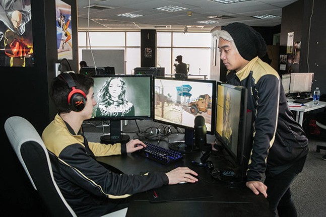 Rob Lee observes Jace Patras playing PUBG at the Pittsburgh Knights' Hazelwood office. - CP PHOTO BY JOHN COLOMBO