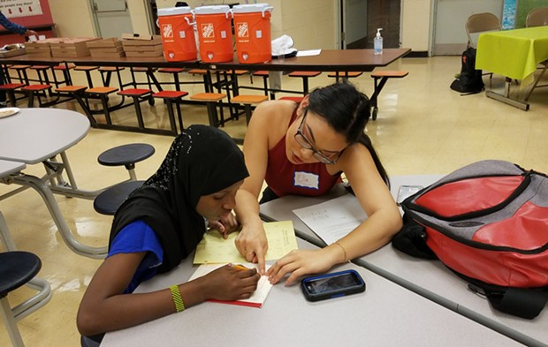 Duquesne University student working with a young refugee - PHOTO COURTESY OF JEWISH FAMILY COMMUNITY SERVICES