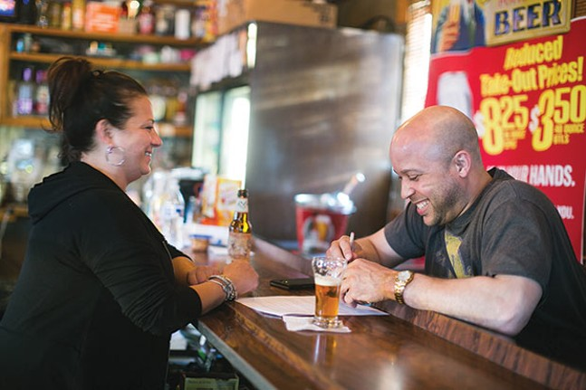 DeeDee, a bartender at Howard's for 15 years, shares a laugh with a customer - CP PHOTO BY JOHN COLOMBO