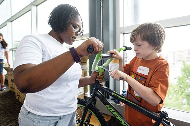 A volunteer helps construct a bicycle at a past Build-a-Bike event. - PHOTO COURTESY OF UNITED WAY OF SOUTHWESTERN PA