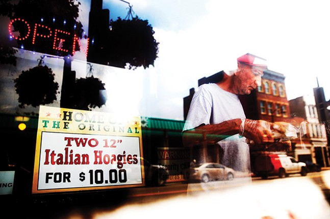 An employee of Joey & Dolly's North Shore Deli prepares hot dogs on East Ohio Street.