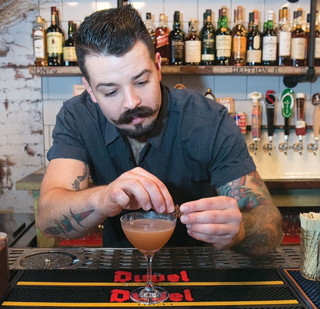 Pork & Beans' bar manager Michael R. Anderson making a Dirty Grove cocktail