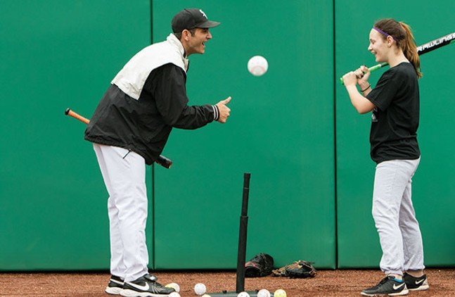 Camp coaches work with hard-of-hearing students on batting, throwing, running and catching in PNC Park's outfield.