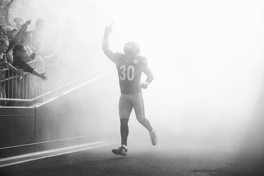 James Conner enters the field amidst a cloud of fog. - CP PHOTO: JARED WICKERHAM