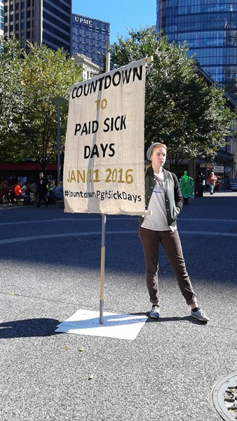 Hannah Vantassel of Pittsburgh UNITED, one of the member groups of the Paid Sick Days Coalition, holds a sign in Market Square to raise awareness of the city's new mandatory sick-days legislation. - PHOTO BY ASHLEY MURRAY