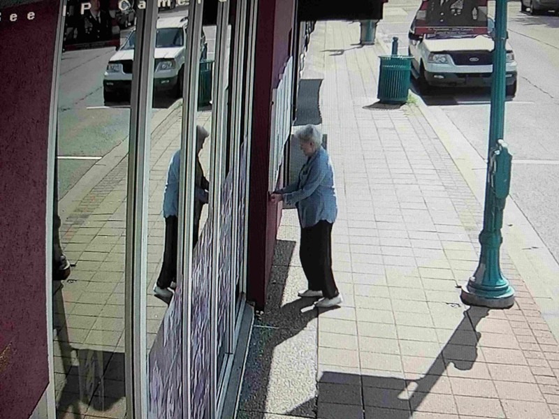 An unidentified woman affixes a sticker to the wall of Carnegie Stages, as seen on a security-camera image - PHOTO COURTESY OF CARNEGIE STAGES