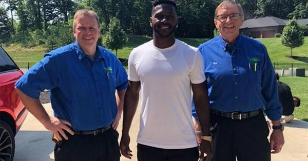 Antonio Brown (center) with Kennihan employees - PHOTO: KENNIHAN PLUMBING, HEATING AND AIR CONDITIONING