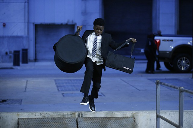 Brandon Terry, drummer for Funky Fly Project, runs and jumps while carrying his drums into the August Wilson Center - CP PHOTO: JARED WICKERHAM