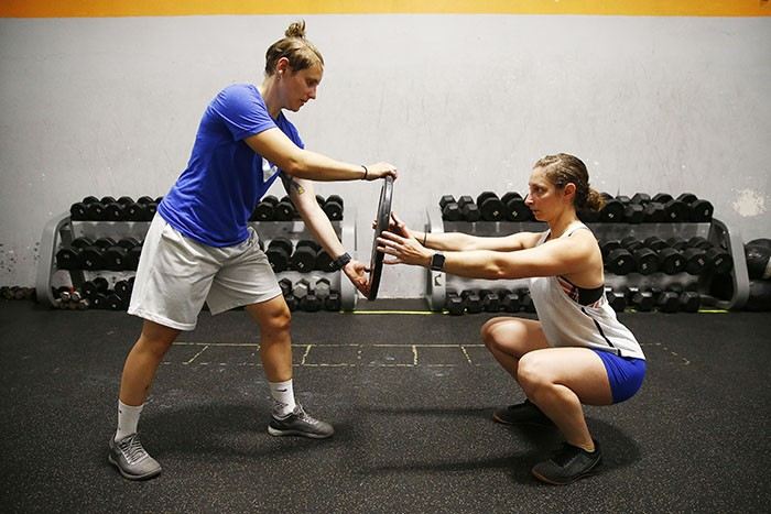 Erica Gadelmeyer, director of operations at the North Side YMCA, does a squat balance workout with Abby Cook during her War Streets Crossfit class. - CP PHOTO: JARED WICKERHAM