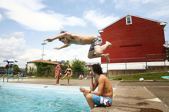 Rich Thewes jumps over his friend, Dustin Klein, before diving into the Bloomfield pool - CP PHOTO: JARED WICKERHAM